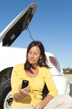 Stressed mature woman breakdown with car on remote road calling for assistance, for help on mobile phone, isolated with blue sky as background and copy space. Stock Photo - 15608239