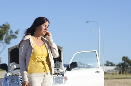 Stressed mature woman breakdown with car on remote road calling for assistance photo