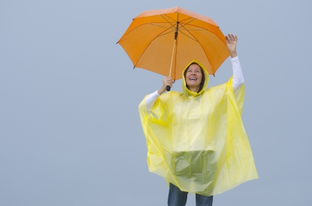 Portrait mature woman standing in the rain, wearing yellow raincoat and orange umbrella, isolated with grey sky as background and copy space