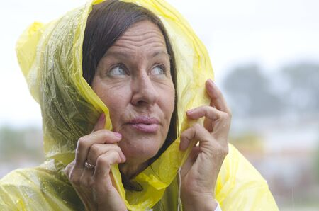 waterproof cape: Portrait mature woman standing in the rain, wearing yellow raincoat, isolated with grey sky as background and copy space