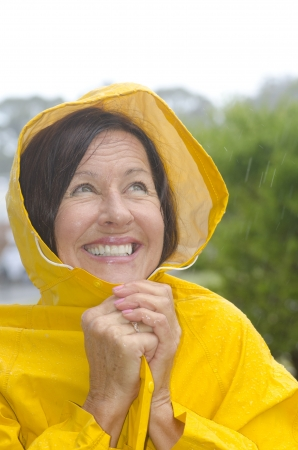 Portrait mature woman standing in the rain, wearing yellow raincoat, isolated with blurred background and copy space