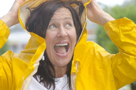waterproof cape: Portrait mature woman standing in the rain, wearing yellow raincoat, isolated with blurred background and copy space