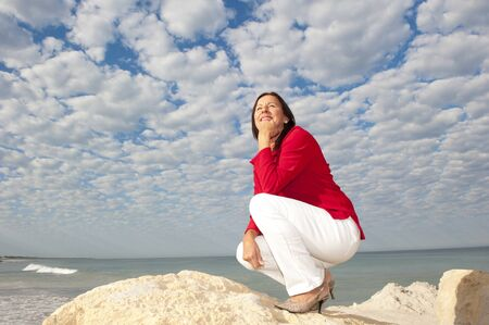Attractive senior woman posing happy and confident at seaside, isolated with ocean and beautiful cloudscape as background and copy space. photo