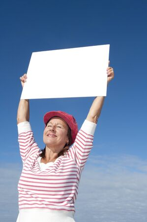 more mature: Portrait of attractive and confident mature woman smiling happy and presenting blank white cardboard outdoor, isolated with blue sky as background and more copy space.