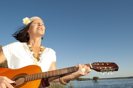 Beautiful mature hippie woman happy relaxed smiling and playing guitar, isolated with flower in hair, blue sky and lake as background and copy space. photo