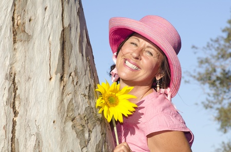 Portrait of sexy mature woman wearing pink hat and sunflower, hugging tree in park, isolated with blue sky as background and copy space. Stock Photo - 15739083