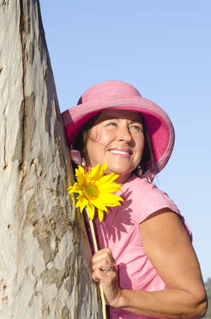 Portrait of sexy mature woman wearing pink hat and sunflower, hugging tree in park, isolated with blue sky as background and copy space. photo