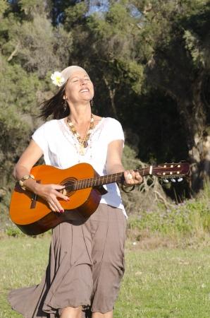 mujer hippie: Retrato de mujer hermosa hippie maduro con la guitarra al aire libre en el parque, disfrutando de estilo de vida de ocio, aislado con vegetaci�n rubor verde como fondo y espacio de la copia. Foto de archivo