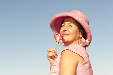 Portrait of sexy mature woman wearing pink hat and rose, isolated with blue sky as background and copy space. photo