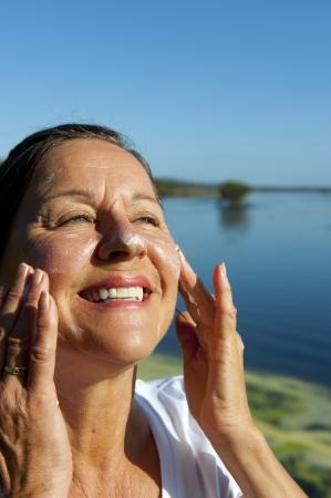 Ritratto di attraente donna matura con creme solari sul viso per proteggersi dal cancro della pelle, isolato con sfondo sfocato e copia spazio. Archivio Fotografico