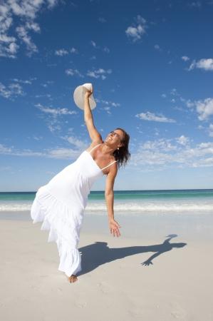 vecchiaia: Sexy bella donna di mezza et� allegro, gioioso in abito bianco estate in spiaggia, isolato con mare e cielo azzurro come sfondo e copia spazio.