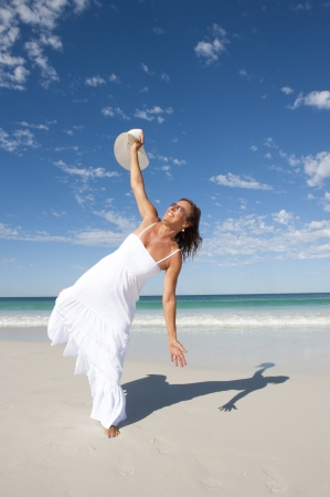 Sexy pretty middle aged woman cheerful, joyful in white summer dress at beach, isolated with ocean and blue sky as background and copy space.