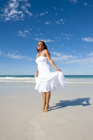 Sexy pretty middle aged woman cheerful, joyful in white summer dress at beach, isolated with ocean and blue sky as background and copy space. photo