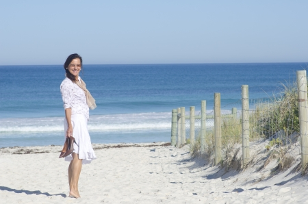 Attractive senior woman happy and joyful at beach, relaxed with high heel shoes in hand, isolated with oceana nd blue sky as background and copy space  photo