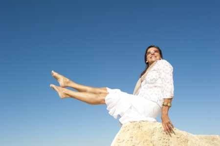 space age: Attractive and fit and healthy looking middle aged woman sitting on rock with legs up in air, isolated with blue sky as background and copy space.
