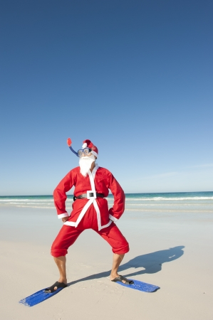 Santa Claus standing with flippers and snorkel at beach Stock Photo