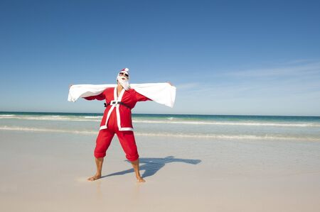 Santa Claus standing with towel at beach photo