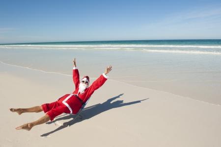 strand australie: Kerstman gelukkig ontspannen zitten met de handen omhoog op het strand