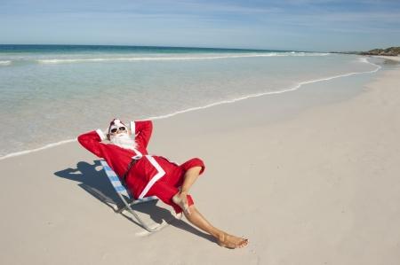 Babbo Natale felice seduta relax con le mani fino in spiaggia Archivio Fotografico
