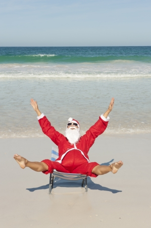 Santa Claus happy sitting with hands up at beach photo
