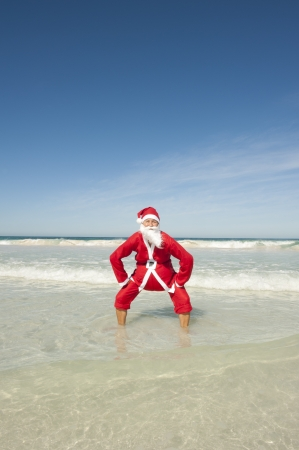 Santa Claus happy standing in shallow water at beach photo