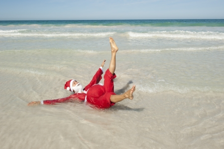 Santa Claus happy lying in shallow water at beach photo
