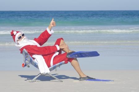 strandstoel: Kerstman zit met flippers en snorkel op het strand Stockfoto
