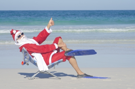 christmas costume: Santa Claus sitting with flippers and snorkel at beach