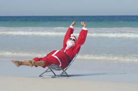 Santa Claus happy relaxed sitting with hands up at beach Stock Photo