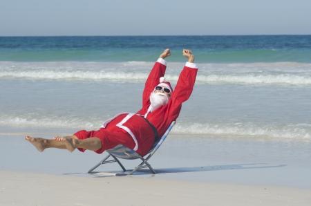 Santa Claus sentado felices relajados con las manos en alto en la playa Foto de archivo - 16375549