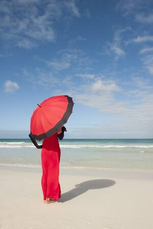 Beautiful lady posing happy smiling in elegant red dress, black gloves and umbrella at beach, isolated with ocean and blue sky as background and copy space. photo