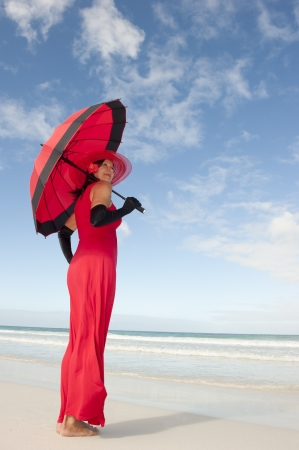 Beautiful looking lady posing happy smiling in elegant red dress, black gloves and umbrella at beach, isolated with ocean and blue sky as background and copy space. photo
