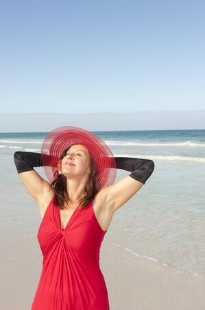 Beautiful looking lady posing happy smiling in elegant red dress and long black gloves at beach, isolated with ocean and blue sky as background and copy space. Stock Photo - 16409987