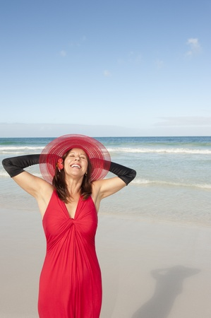 Beautiful looking lady posing happy smiling in elegant red dress and long black gloves at beach, isolated with ocean and blue sky as background and copy space. Stock Photo - 16409988