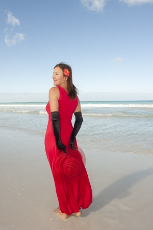 sexy mature women: Beautiful looking lady posing happy smiling in elegant red dress and long black gloves at beach, isolated with ocean and blue sky as background and copy space. Stock Photo
