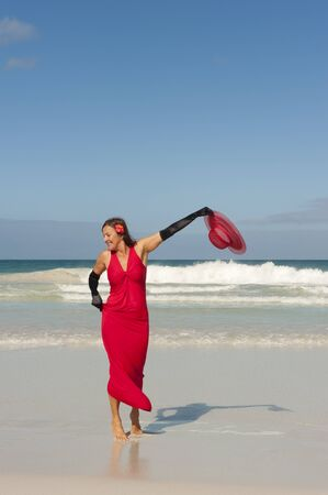 Sexy looking lady posing happy smiling in elegant red dress and long black gloves dancing at beach, isolated with ocean and blue sky as background and copy space. photo
