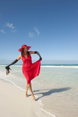 Sexy looking lady posing happy smiling in elegant red dress, long black gloves and high heels at beach, isolated with ocean and blue sky as background and copy space. photo