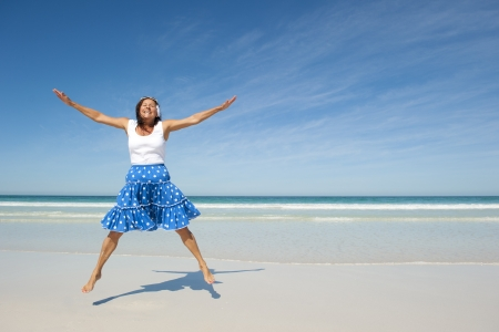 woman arms up: Beautiful looking and active senior woman enjoying retirement, jumping at beach, isolated with ocean and blue sky as background  Stock Photo
