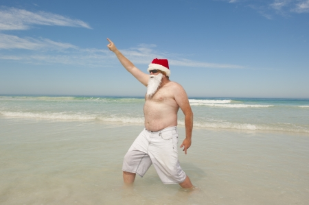 Relaxed and confident Santa Claus enjoying tropical holiday vacation at beach, isolated with ocean and blue sky as background and copy space.