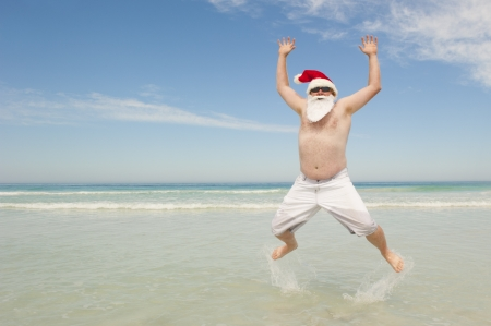 Felice gioioso e allegro Babbo Natale in vacanza estiva, saltando in acque poco profonde alla spiaggia tropicale