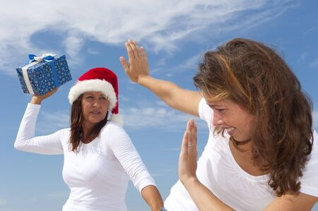 Two attractive women  girls at carribean beach holiday with christmas box, close up, isolated with blue sky as background and copyspace. photo