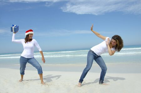 argumento: Dos mujeres atractivas en el caribe playa, divirtiéndose con la caja de navidad, aislados con el océano y el cielo azul como fondo y copyspace.