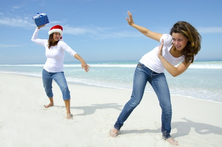 Two attractive women at carribean beach holiday with christmas present, isolated with ocean and blue sky as background and copyspace. photo