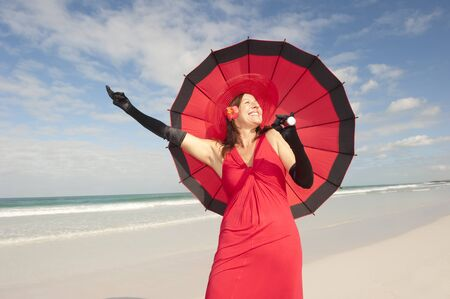 Beautiful elegant mature woman happy smiling in long red dress, hat, parasol and black gloves at tropical beach, isolated with ocean and blue sky as background and copy space. Stock Photo - 16517363