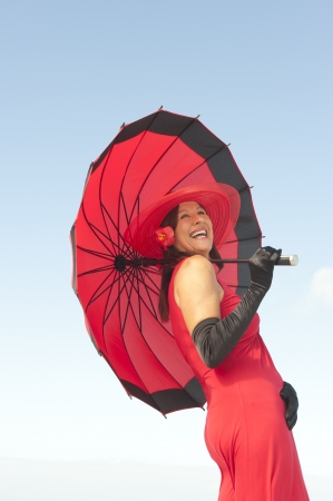 Beautiful elegant mature woman happy smiling in long red dress, hat, umbrella and black gloves, isolated with ocean and blue sky as background and copy space. photo