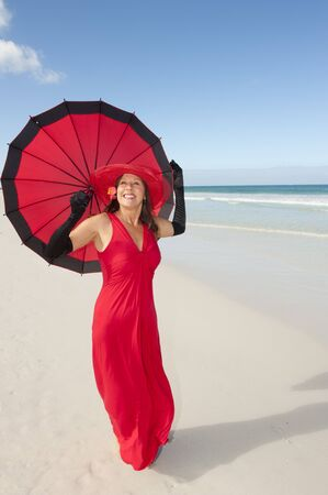 Beautiful elegant mature woman happy smiling in long red dress, hat, umbrella and black gloves bare feet at tropical beach, isolated with ocean and blue sky as background and copy space. photo