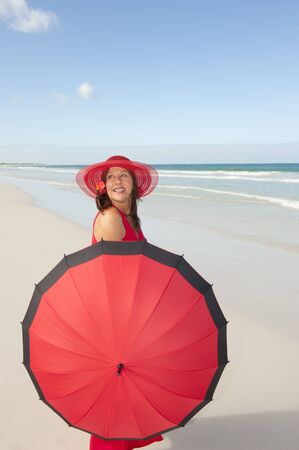 Beautiful elegant mature woman happy smiling in long red dress, hat, parasol and black gloves bare feet at tropical beach, isolated with ocean and blue sky as background and copy space. photo