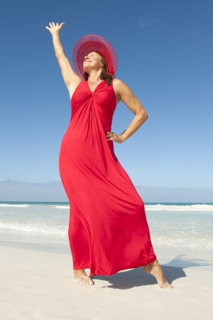 Beautiful elegant happy mature woman in long red dress and hat  at tropical beach, isolated with ocean and blue sky as background and copy space. Stock Photo - 16517358