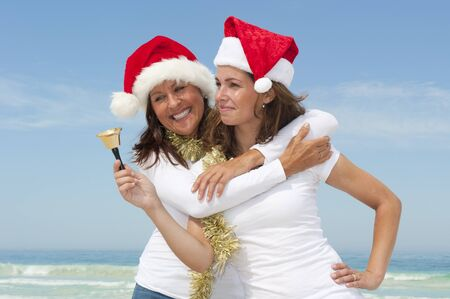 Mother and daughter, two happy and attractive looking women celebrating christmas wearing santa claus hats at tropical beach, isolated with ocean and blue sky as blurred background and copy space. photo