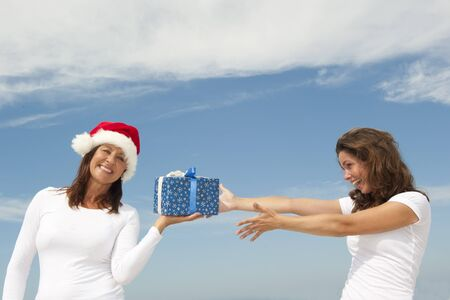 Beautiful looking and happy smiling mature woman wearing Santa Claus christmas hat is giving present to younger girl, isolated with blue sky as background and copy space. photo